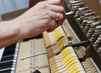 Piano technician adjusts the tuning pins on an upright piano.