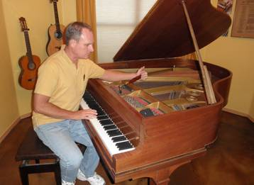 Tim Rainwater works on tuning a baby grand piano in a home music room.